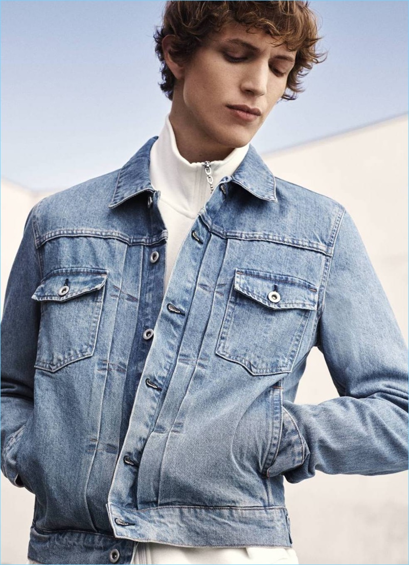Model Xavier Buestel sports a denim jacket and full-zip cardigan from H&M.