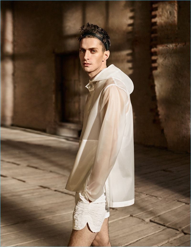 Making quite the style statement, Matthew Bell wears a white raincoat and shorts from H&M Studio.