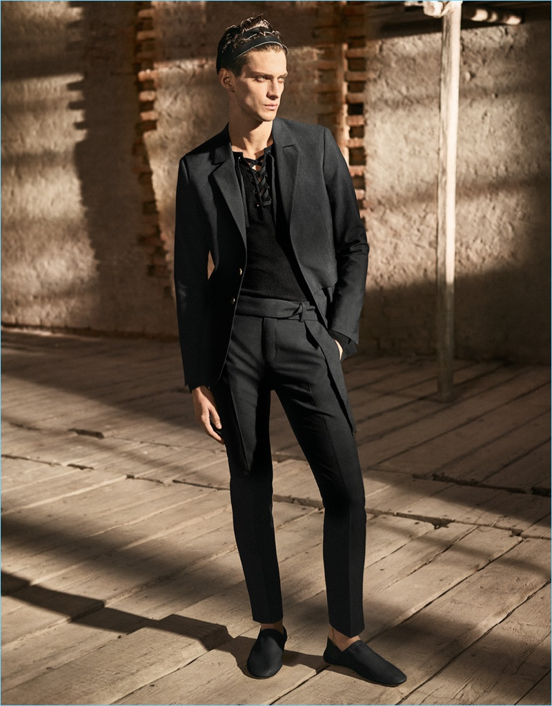 Dressed in head to toe black, Matthew Bell dons a blazer, trim trousers, and a lace-up top by H&M Studio.