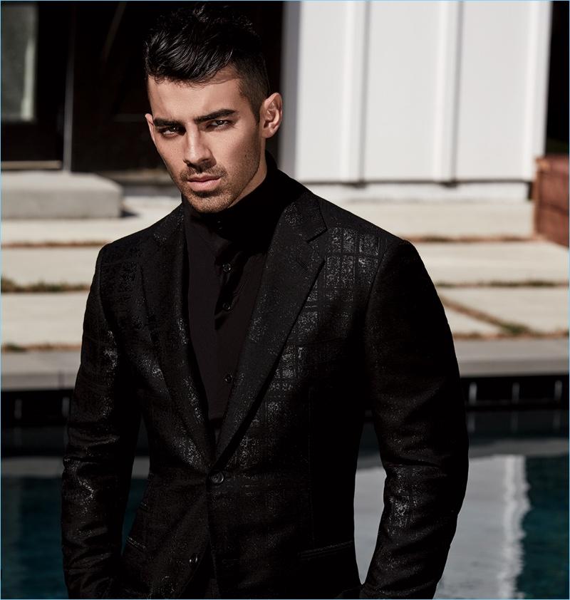 Striking in a photo, Joe Jonas wears a shirt, jacket, and trousers by Hermes.