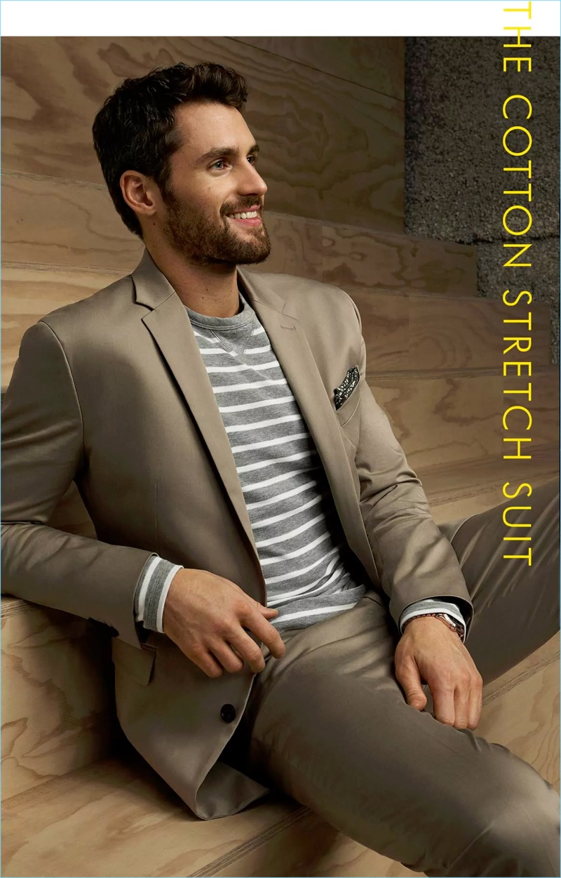 All smiles, Kevin Love wears a neutral slim lapel suit with a striped pullover.