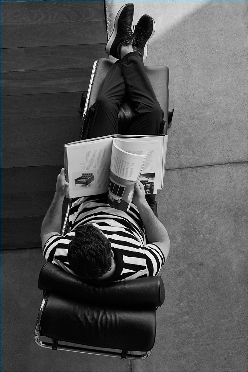 Reading a book, Justice Joslin wears a striped polo, cargo trousers, and sneakers from Massimo Dutti's limited edition Soft Collection.