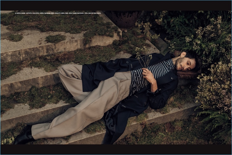 Relaxing, Pierre Niney wears a trench coat and striped turtleneck by Lanvin with oversized Fendi trousers.