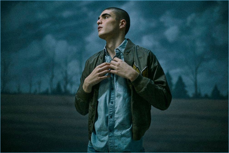 Appearing in a moody image, Diego Villarreal sports a bomber jacket, chambray shirt, and jeans from RRL.