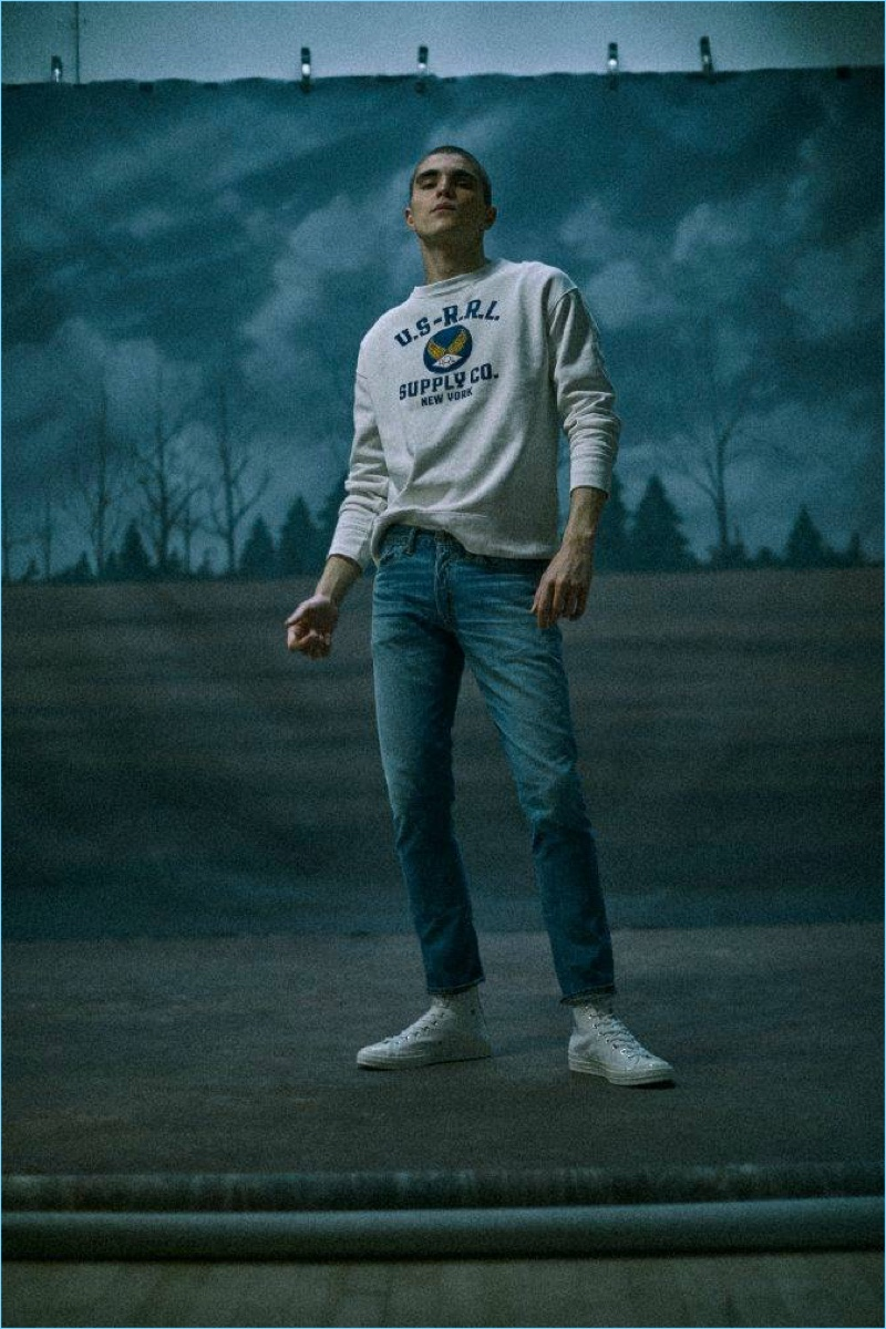 Embracing an all-American flair, Diego Villarreal wears a RRL logo fleece sweatshirt and denim jeans with Comme des Garçons Play sneakers.
