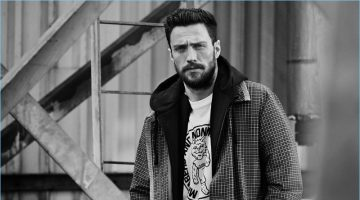 Aaron Taylor-Johnson sports a Prada checked wool coat with a Vetements + Champion hoodie and a Stella McCartney graphic t-shirt.