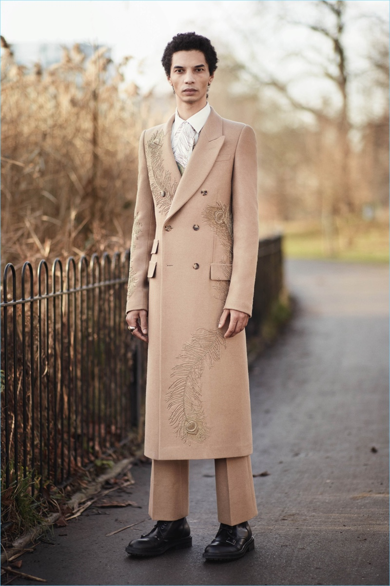 British brand Alexander McQueen commits to a camel hued story with a long double-breasted overcoat and pleated trousers.