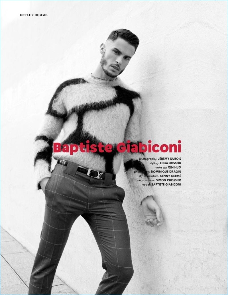 French model Baptiste Giabiconi dons a giraffe print sweater with windowpane print trousers and a logo belt by Louis Vuitton.