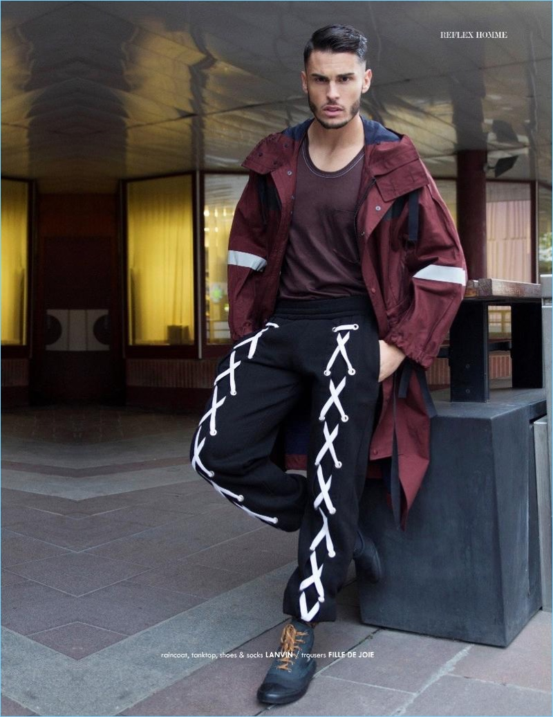 Starring in an editorial for Reflex Homme, Baptiste Giabiconi wears Fille de Joie joggers with a raincoat, tank, and shoes by Lanvin.