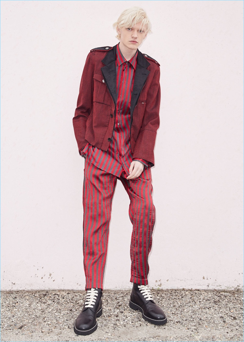 Embracing a monochromatic flair, Turner Barbur wears an Ann Demeulemeester blouson and Maison Margiela combat boots. Turner also dons a red and grey striped shirt with trousers by Ann Demeulemeester.