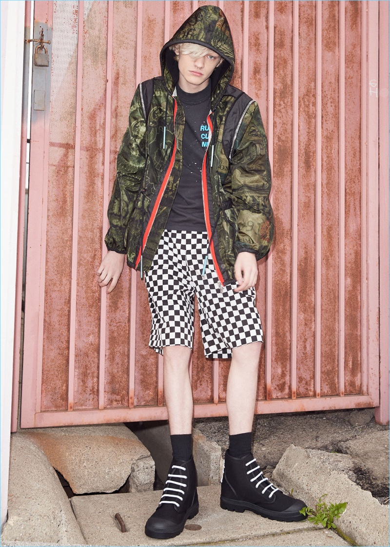 Mixing prints, Turner Barbur rocks a printed lightweight jacket by Givenchy. Turner also wears a Satisfy cult moth eaten sleeveless tee with Givenchy checkerboard prints shorts. The model's look is finished with Givenchy canvas star sneaker boots.