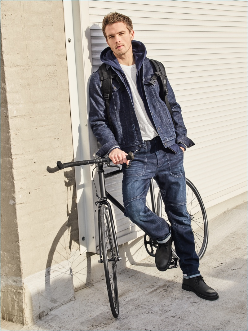 A casual vision, Benjamin Eidem wears a denim jacket and distressed jeans, layered with an essential hoodie.