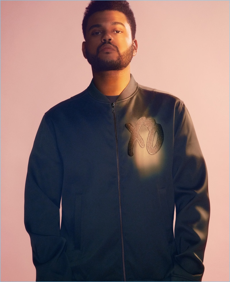 Front and center, The Weeknd wears a bomber jacket with an XO on the chest.