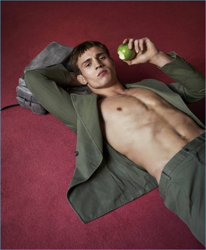 Taking a bite of a green apple, Julian Schneyder wears a look from Tod's.