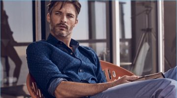 Relaxing, Ben Hill wears trousers and a navy chambray shirt with a star print from J.Hilburn.