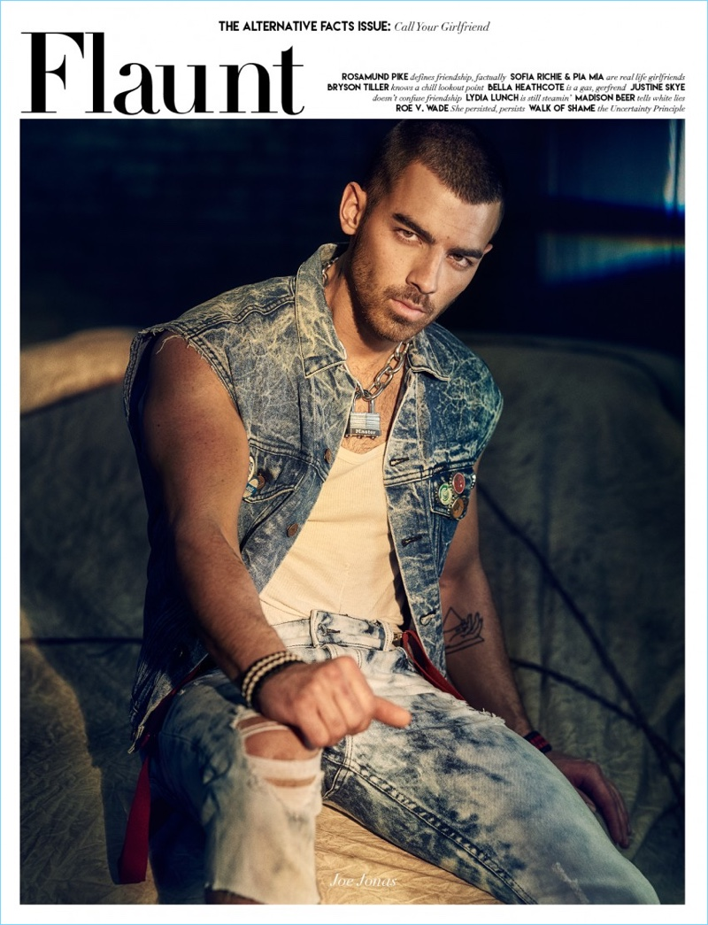 Joe Jonas covers the latest issue of Flaunt magazine. The singer sports a vintage GUESS vest with a tank and suspenders. Jonas also sports ripped GUESS jeans.
