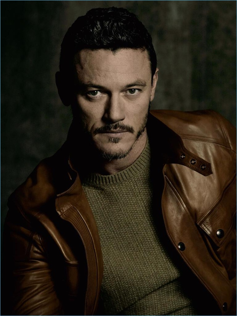 Ready for his close-up, Luke Evans dons a crewneck sweater and brown leather jacket by Ralph Lauren Purple Label.