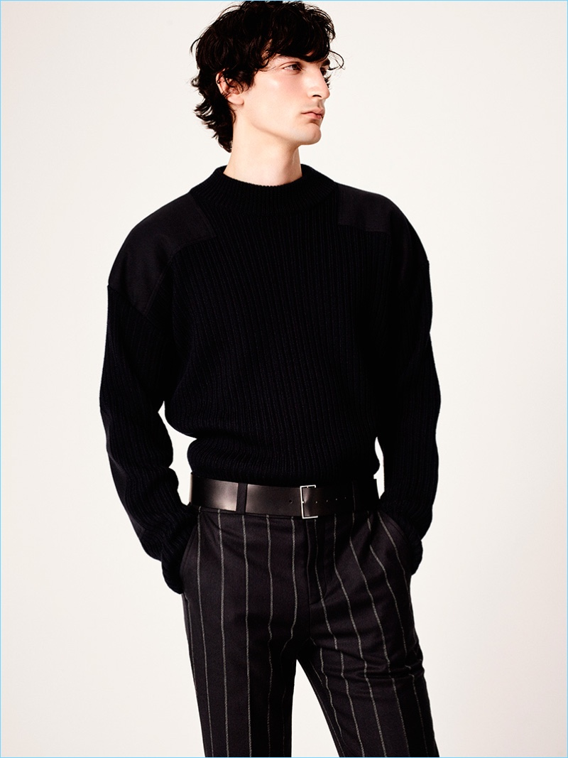 Model Luca Lemaire dons a sculpted sweater with pinstripe trousers from Sandro's fall-winter 2017 men's collection.
