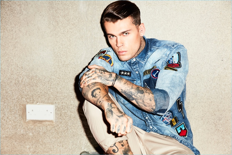 Wearing denim and chinos, Stephen James is pictured in a patch adorned Replay shirt.