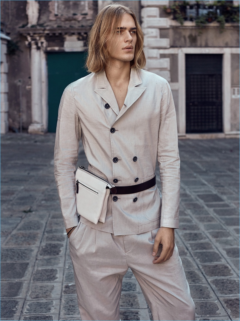 Taking to the streets of Venice, Ton Heukels dons a double-breasted Giorgio Armani suit with a Canali bag.