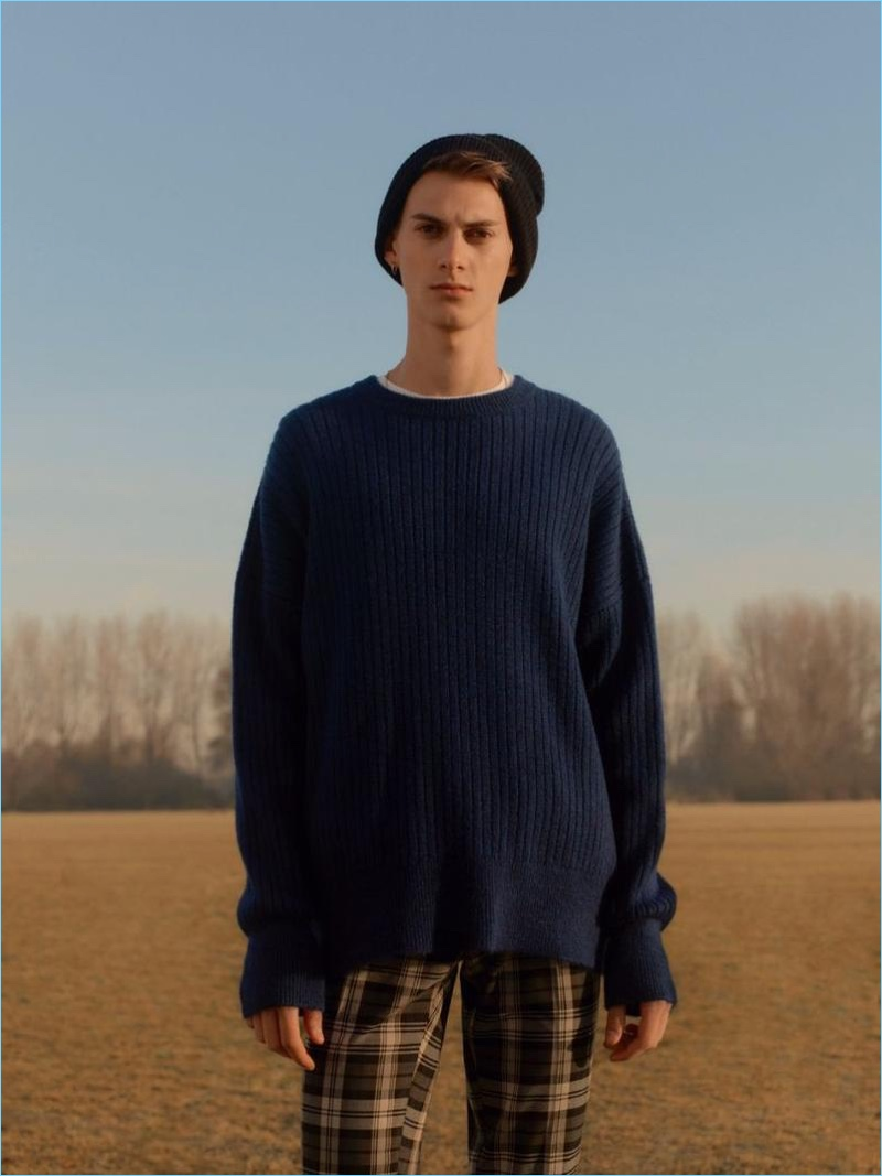 Derian Unterweger rocks a navy ribbed drop shoulder sweater with plaid pants by Topman.
