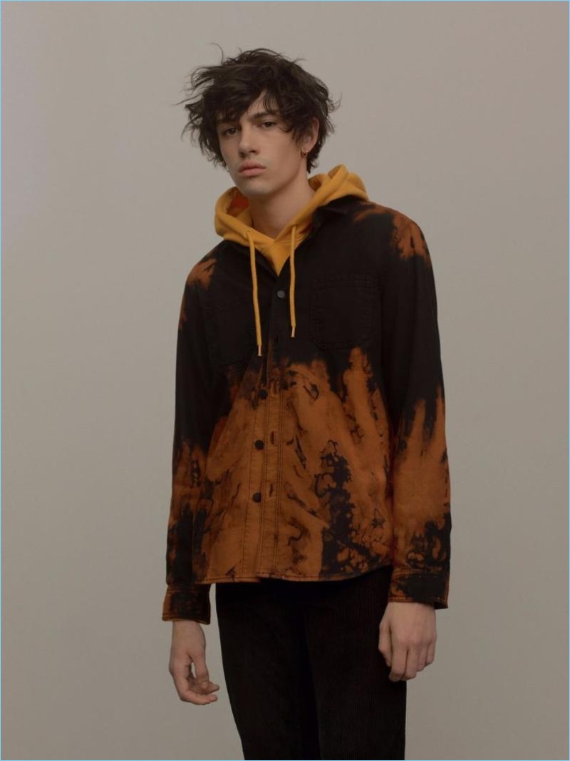 Going casual, Basti Robert wears a mustard yellow overhead hoodie with a black and orange sunset denim shirt by Topman.