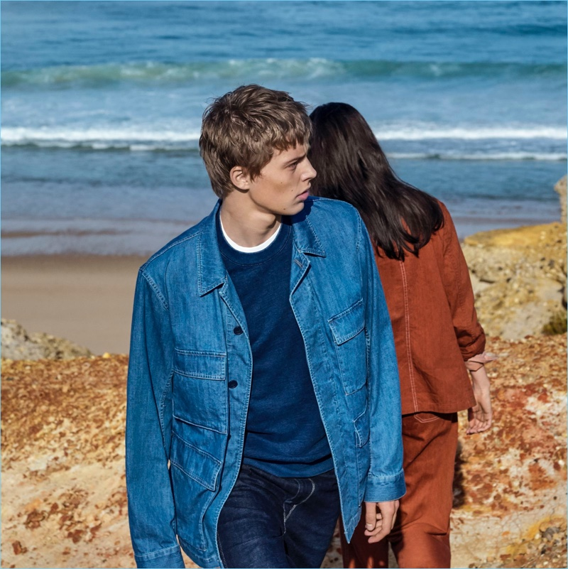 Make a casual blue statement in Uniqlo U's work jacket, crewneck sweater, and denim jeans.