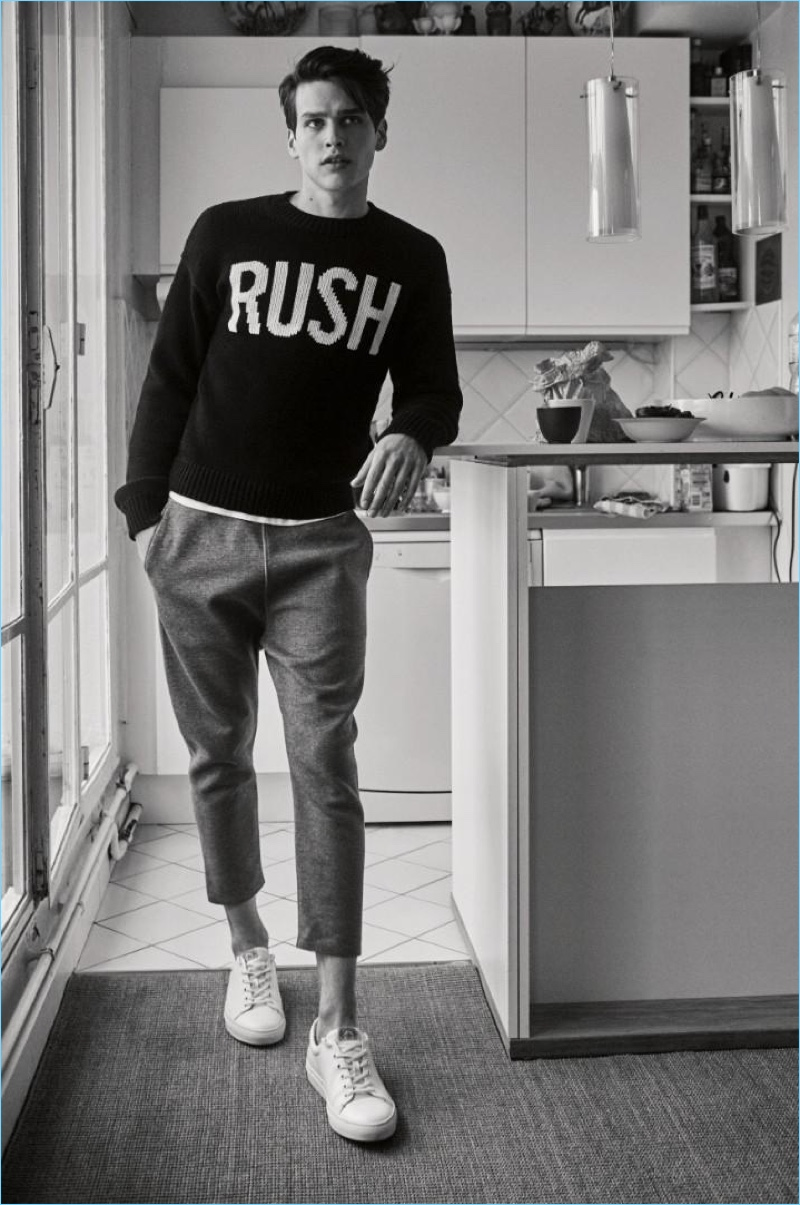 Appearing in a black and white photo, Simon van Meervenne wears a 'RUSH' sweater with cropped trousers by Zadig & Voltaire.
