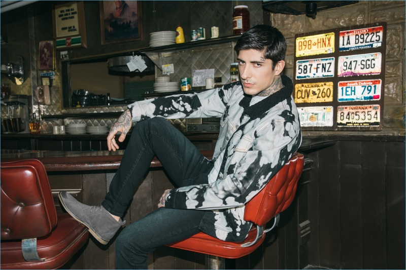 Relaxing at a diner, Daniel Bamdad sports a bleached jacket with distressed jeans and chukka boots from boohooMAN.