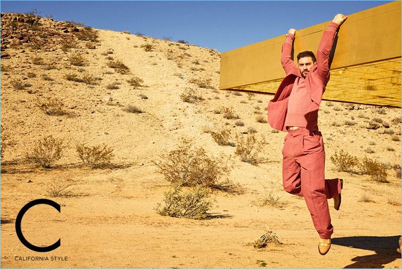 Taking to the desert, Aaron Taylor-Johnson sports a Bottega Veneta sweater and suit with Santoni shoes.