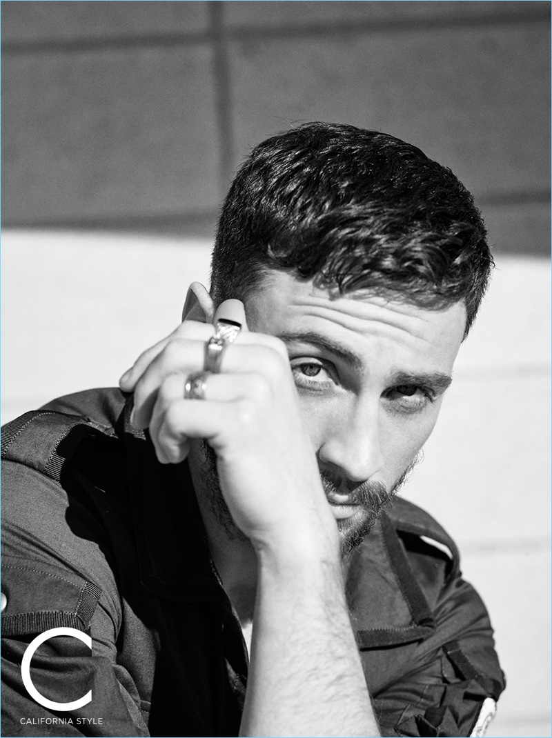 Appearing in a black and white photo, Aaron Taylor-Johnson wears a Moncler Gamme Bleu shirt with a David Yurman ring.