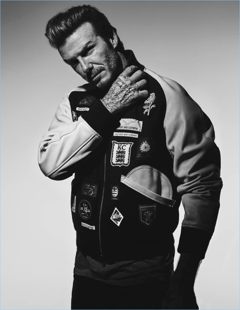 Front and center, David Beckham wears a Kent & Curwen varsity bomber jacket, Balmain t-shirt, and Saint Laurent jeans.