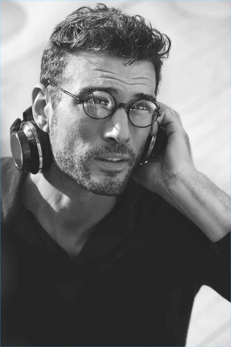Tristan wears round frame Giorgio Armani AR 5069J glasses.