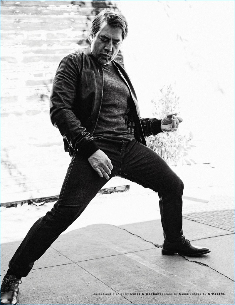 Striking a dance move, Javier Bardem dons a t-shirt and jacket by Dolce & Gabbana with Gucci jeans and O'Keeffe shoes.