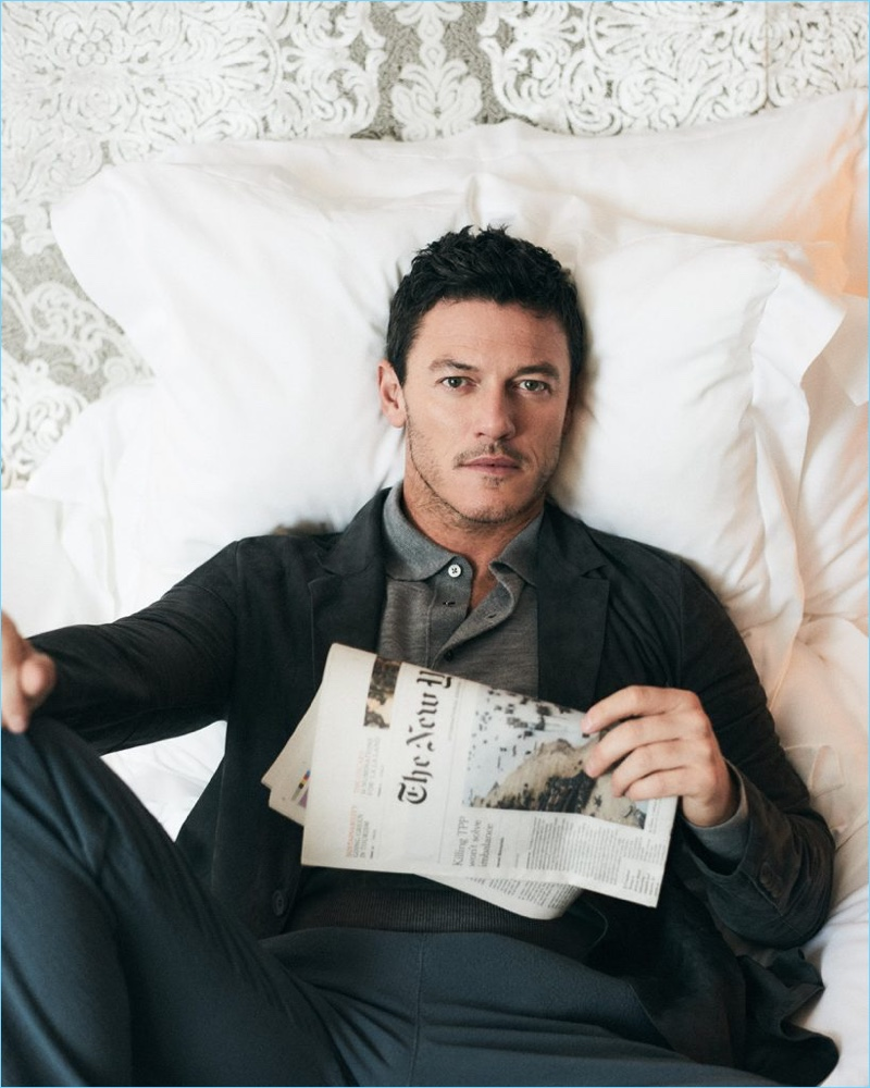Lounging in bed, Luke Evans wears a Hardy Amies polo with a grey blazer and trousers by Giorgio Armani.