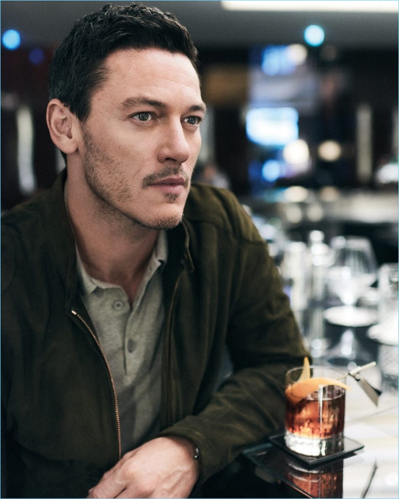 Enjoying a drink, Luke Evans dons a Private White V.C. suede bomber jacket and Thom Sweeney polo.