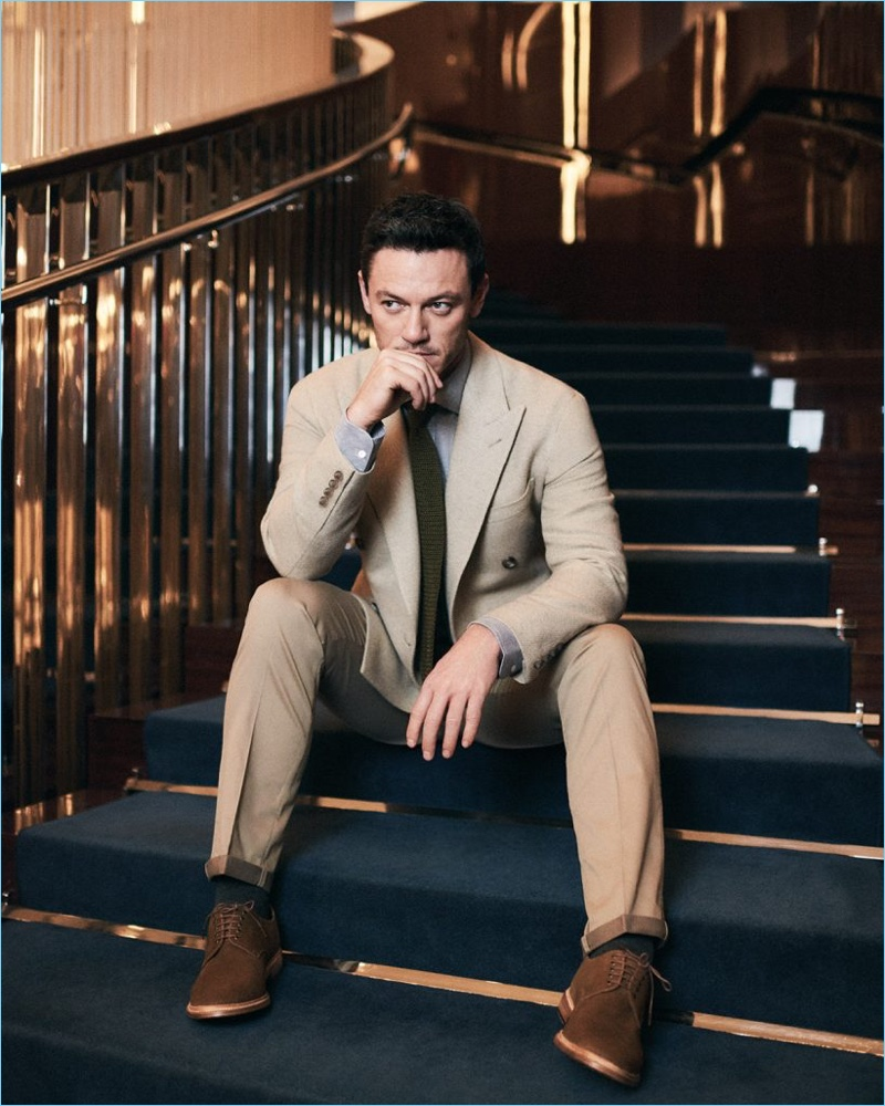 Stealing a moment, Luke Evans sports a shirt and double-breasted jacket by Ralph Lauren Purple Label. Evans also wears a New & Lingwood tie, Hackett London chinos, and Grenson shoes.