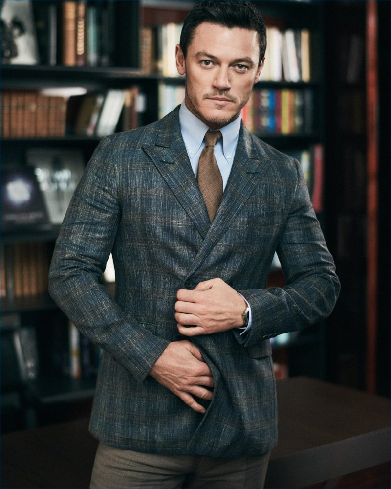 Donning a double-breasted jacket by Dunhill, Luke Evans also wears a Turnbull & Asser shirt, Drake's tie, and Brunello Cucinelli trousers.