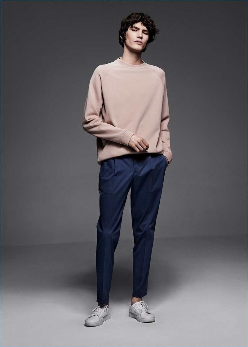 Embracing a casual look, Elias de Poot dons a Mango Man pink sweatshirt $49.99, slim-fit cotton suit trousers $89.99, and canvas sneakers $35.99.
