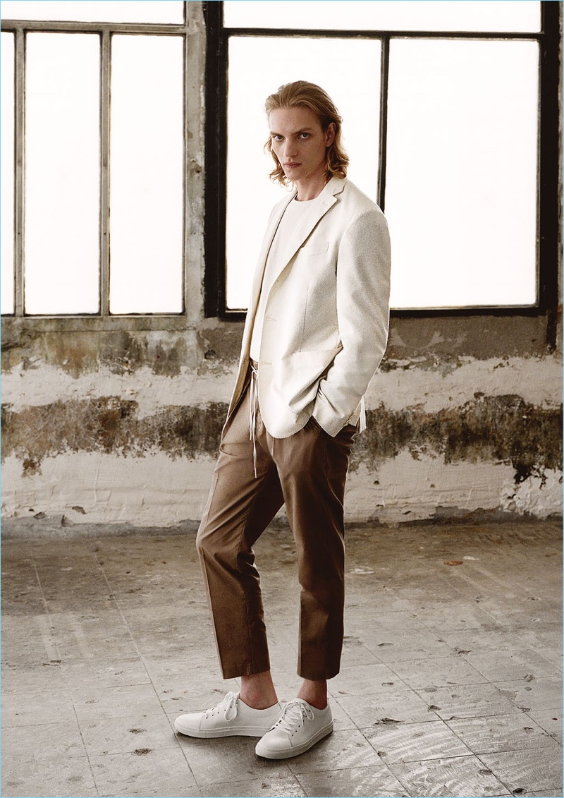 Model Paul Boche embraces a neutral color palette. He wears a Mango Man slim-fit textured blazer $199.99, v-neck t-shirt $15.99, pleated trousers $69.99, and lace-up leather sneakers $69.99.