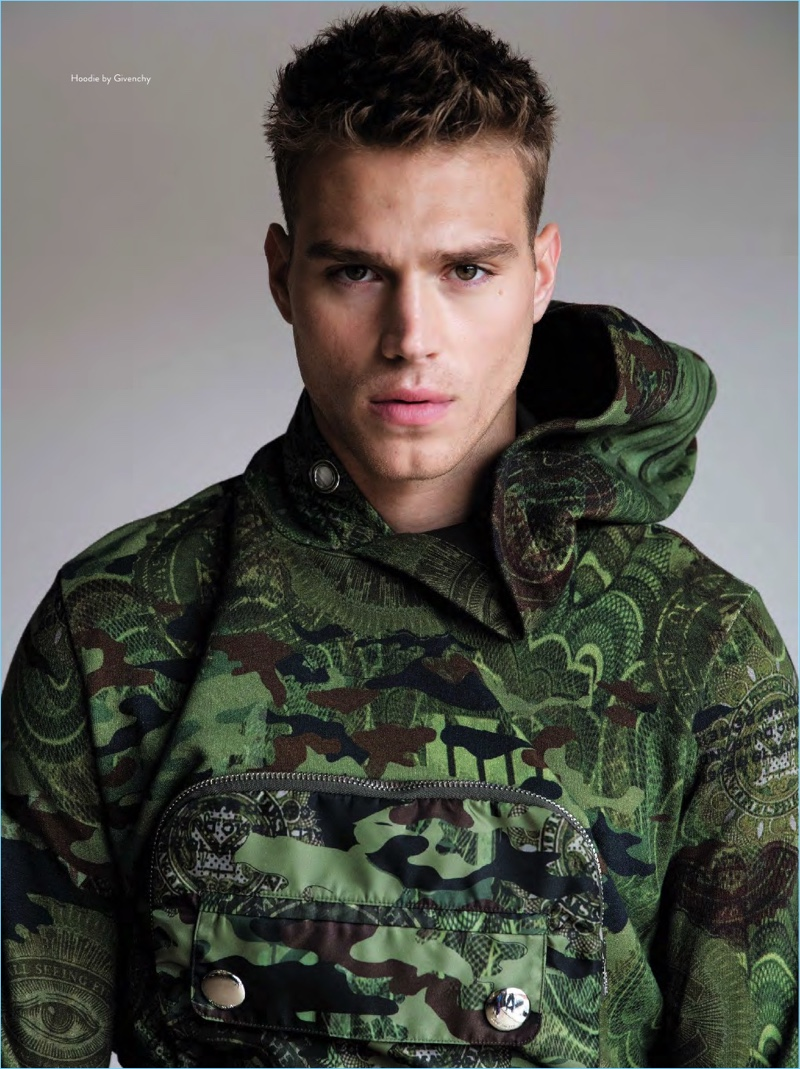 Front and center, Matthew Noszka goes sporty in a camouflage hoodie by Givenchy.