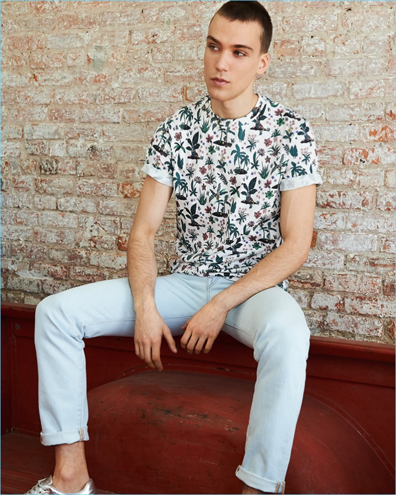 Going casual, Marc Lüloh wears an allover floral print tee and tapered jeans from PS by Paul with Paul Smith metallic leather sneakers.