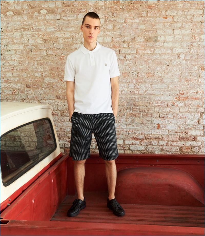 Front and center, Marc Lüloh rocks a regular fit polo, black dot shorts, and sneakers from PS by Paul Smith.