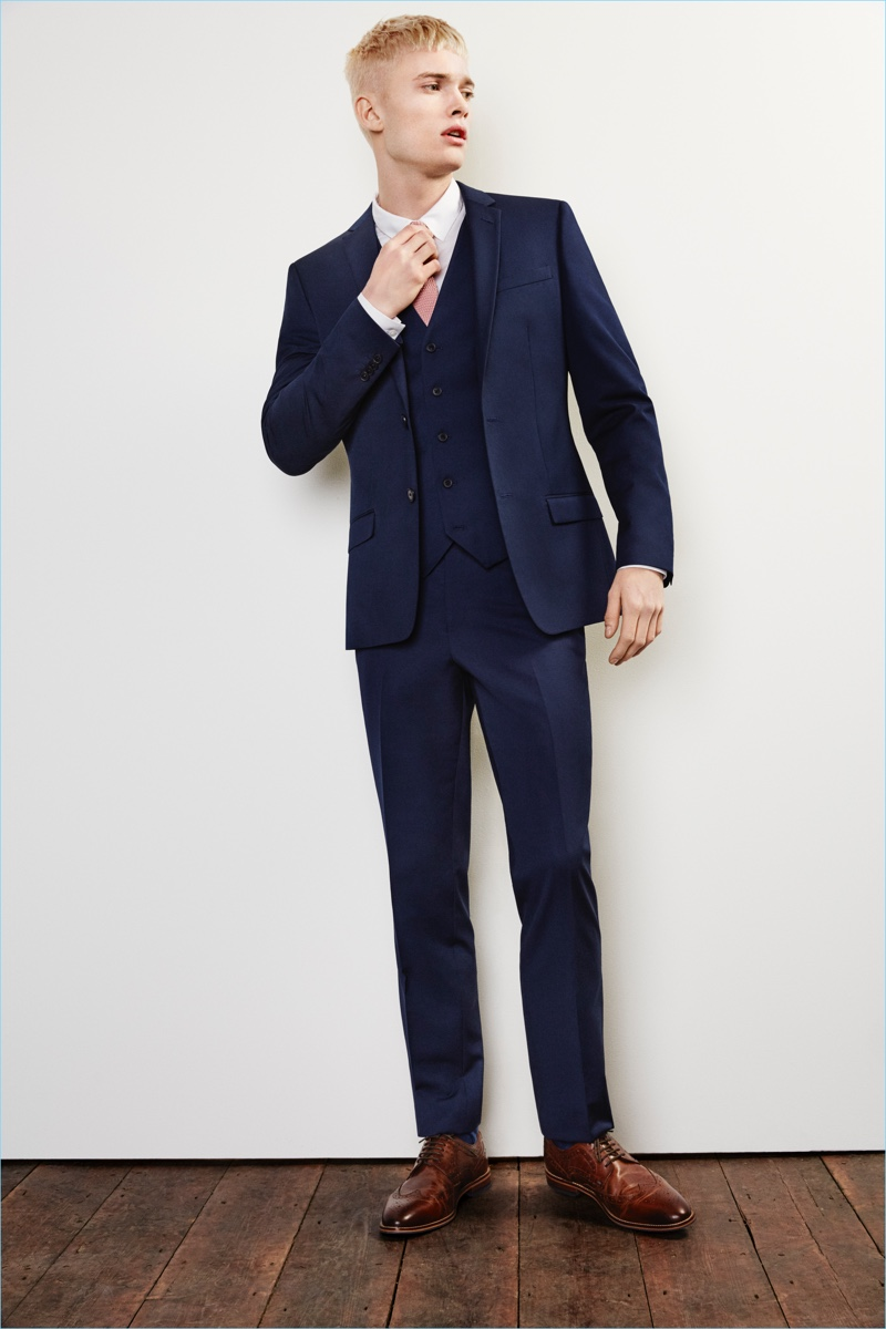 Make a classic statement in a dark blue River Island slim-fit suit jacket $130, vest $70, and pants $70.