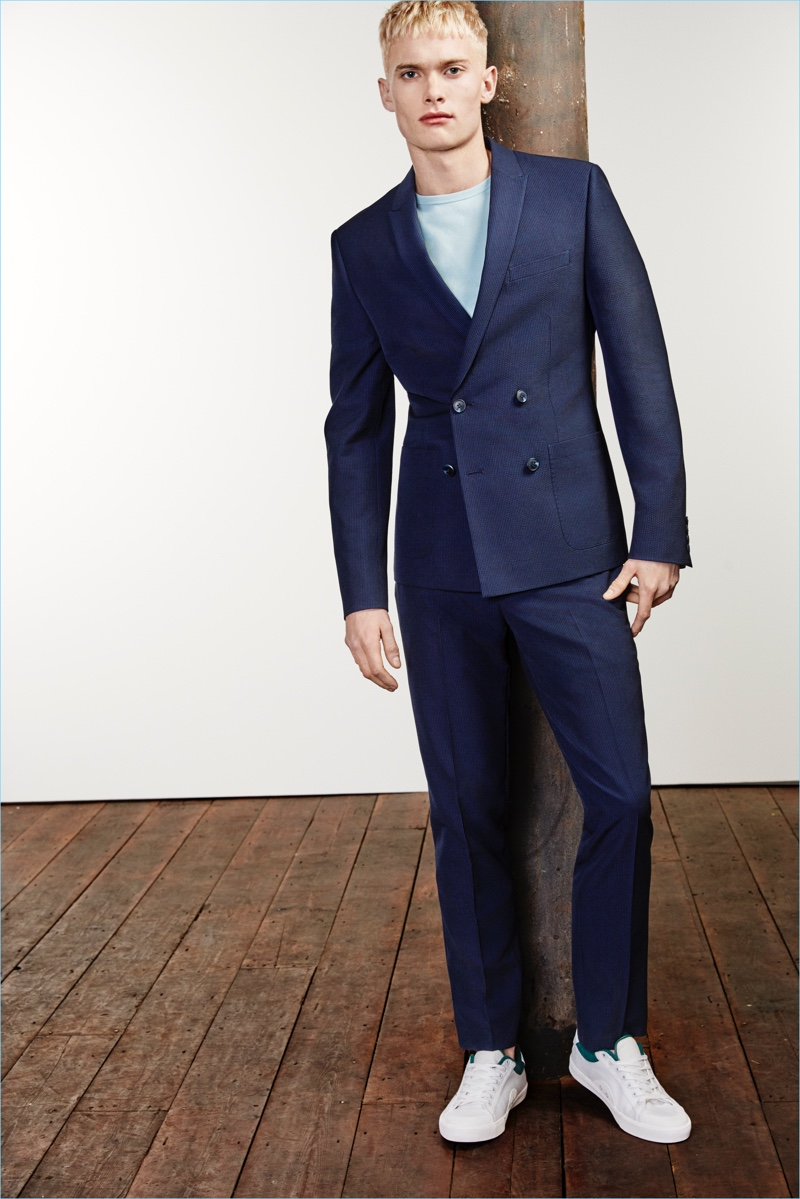 A t-shirt and sneakers contributes to a casual suiting look, which features a navy River Island double-breasted suit jacket $170 and cropped trousers $80.