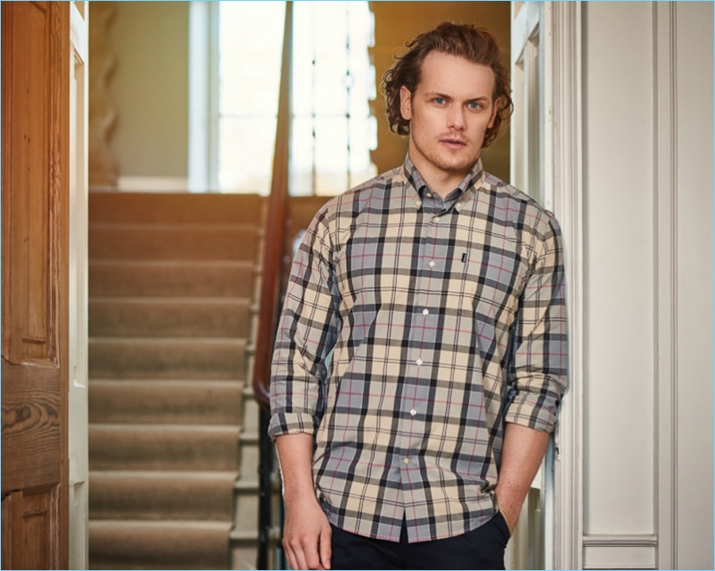 8056999c937 Actor Sam Heughan dons a Barbour tartan shirt  95.13 for the label s  spring-summer 2017