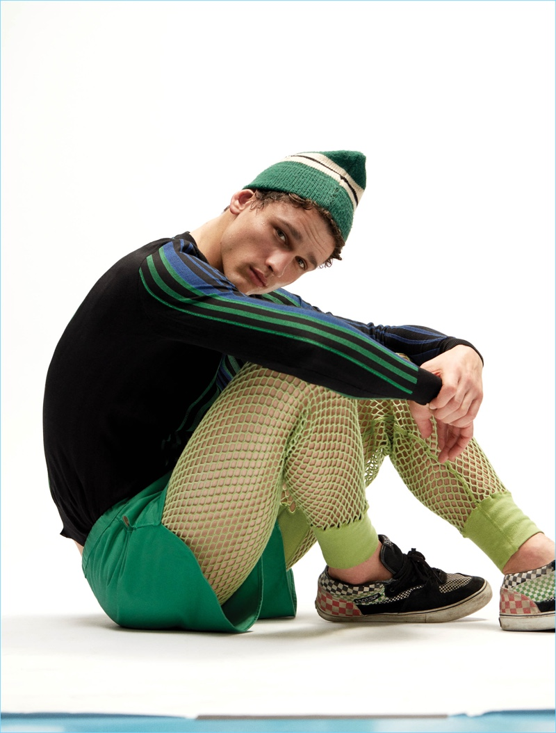 Simon Nessman sports a Balmain sweater with Acne Studios shorts and vintage Vans sneakers.