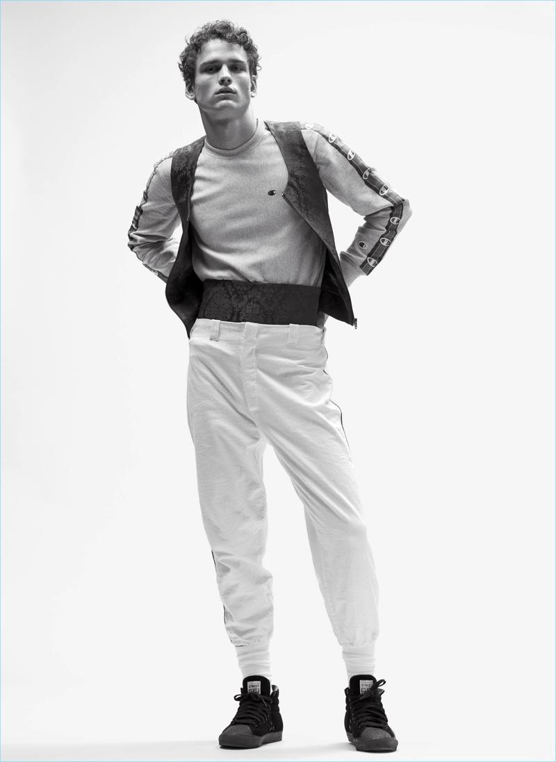 Standing tall, SImon Nessman sports a Champion sweatshirt with a Balenciaga vest and cummerbund.