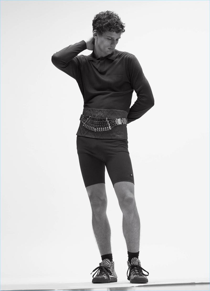 Appearing in an editorial for VMAN, Simon Nessman wears a Versace top and shorts with a Balenciaga cummerbund.
