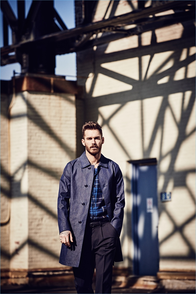 Model David Alexander Flinn sports a Mackintosh Dalblair trench coat $1,998 in chambray navy. David also wears a navy and black short-sleeve camp collar shirt $128 and trousers $248.